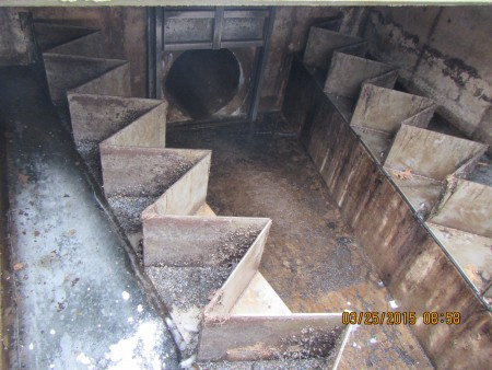 "Inside the Outlet Structure.  The zigzag metal contraption is ""the weir.""  Water will naturally fall over the weir when the lake surpasses 902.5'. Water then flows into the 36"" diameter pipe which travels nearly a ½ mile underground before reaching daylight, or the beginning of the Outlet Channel.  The Outlet Channel then flows approximately 8 miles before reaching the MN River."