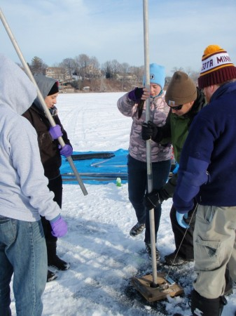 The team uses an assemblable pole to drive the sediment coring device into the lake bed.