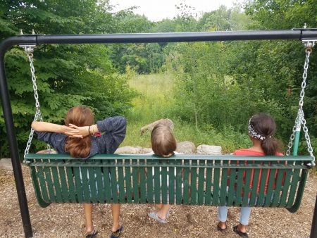 Three kids sitting on bench swing looking out over wetland at Rice Lake Park.